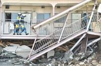 倒壊したアパートを捜索するため、バールでドアをこじ開ける警察官=熊本県益城町で2016年4月17日午後2時40分、須賀川理撮影