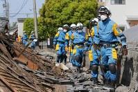 応援部隊による一斉捜索が始まり、倒壊した家屋付近を調べる愛知県警の特別救助班=熊本県益城町で2016年4月17日午前9時46分、三村政司撮影