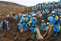 土砂崩れ現場で行方不明者を捜す警察官。周辺で住宅3軒が完全に埋まっている=熊本県南阿蘇村黒川地区高野台で2016年4月17日午後5時45分、丸山博撮影