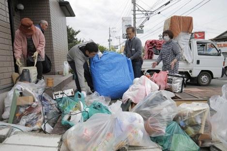 家族総出でゴミを片付ける被災者=熊本県益城町で2016年4月18日午後2時7分、三村政司撮影