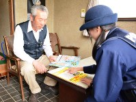 チラシを使って注意を呼びかける警察官(右)=前橋市東上野町で