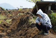The son of a man still missing after a landslide in Minamiaso, Kumamoto Prefecture, covers his face with his hand as he looks at the disaster scene, on April 19, 2016. (Mainichi)
