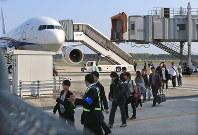再開した熊本空港に到着した第1便から降り、空港関係者の誘導でターミナルビルを迂回する乗客たち=熊本県益城町で2016年4月19日午前7時47分、兵藤公治撮影