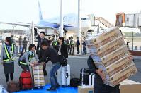 再開した熊本空港に到着した第1便から食料などの物資を運び出す乗客ら=熊本県益城町で2016年4月19日午前7時54分、兵藤公治撮影