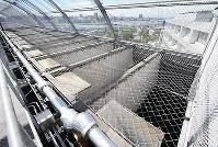 刑務官の監視用通路から見た、東京拘置所の最上階に並ぶ手狭な運動場。上部は二重の金網に覆われ、場内から空は格子状にしか見えない=東京都葛飾区の東京拘置所で2012年10月4日、須賀川理撮影