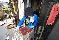 倒壊の危険がある自宅からアルバムや貴重品を運び出す山本洋子さん(28)。家族経営の店も自宅も全壊した山本さんは「家族全員の仕事がなくなってしまって不安です」と話した=熊本県益城町で20日午前10時12分、兵藤公治撮影
