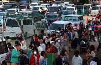 夕飯の配食に並ぶ大勢の人たち。奥のグラウンドには車中泊をする人たちの車が並んでいた=熊本県益城町の広安小学校で2016年4月20日午後5時49分、兵藤公治撮影(一部画像を処理しています)