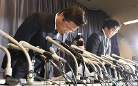 記者会見で頭を下げる三菱自動車の相川哲郎社長(左)=東京・霞が関の国土交通省で2016年4月20日午後5時4分、竹内幹撮影