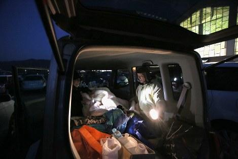 避難所となっている小学校にとめた車の中で寝るため準備をする森幸一さん(82)(右)と妻の恵子さん(77)。多くの人が過ごす体育館(右奥)や校舎は「知らない人も多いし、寒そうだから」と車中泊を続けている。自宅は停電が続き、恵子さんは「年寄りにはこたえる。復旧が待ち遠しい」と話した=熊本県阿蘇市の市立一の宮小学校で2016年4月19日午後7時21分、和田大典撮影