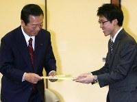 井山裕太名人(右)からプレゼントを手渡され、笑顔を見せる小沢一郎氏=東京都千代田区の日本棋院で2010年1月10日午後5時3分、梅田麻衣子撮影