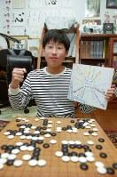 囲碁プロ棋士としてのデビュー前、自宅で取材に応じる当時12歳の井山裕太さん。小学校のクラスメートから贈られた応援の色紙を持ちながら「プロとして頑張る」とガッツポーズ=東大阪市で2002年2月22日、小関勉撮影