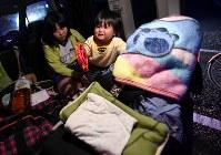 姉の大山愛歩さん(12、左)と車内で過ごす裕己ちゃん(11カ月)。日が沈み、周囲が暗くなると裕己ちゃんは不安で泣いてしまう=熊本県益城町で2016年4月20日午後7時19分、久保玲撮影