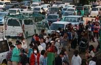 晩ご飯の配食に並ぶ大勢の人たち。奥にはグラウンドに駐車された車中泊をする人たちの車が並んでいた=熊本県益城町の広安小学校で2016年4月20日午後5時49分、兵藤公治撮影