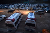 車中泊の車も並ぶ南阿蘇村長陽体育館前のグラウンドに止められた救急車。村内で救急搬送が必要となったときのために待機しているという=熊本県南阿蘇村で2016年4月20日午後7時2分、徳野仁子撮影