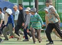 避難所に隣接するテニスコートで、エコノミークラス症候群防止のウォーキング教室が開かれ体を動かす人たち=熊本県益城町で2016年4月20日午後4時28分、野田武撮影