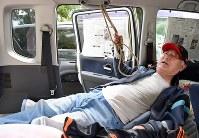 南阿蘇村役場長陽庁舎の駐車場で車中泊を続ける神毛(こうげ)信(あきら)さん(79)。体を起こすときなどのサポートのために縄を取り付けたり、毛布で高さを調整したりと工夫を重ね「これで少し快適になった」と話した=熊本県南阿蘇村で2016年4月20日午後3時38分、徳野仁子撮影