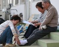 避難所でのエコノミークラス症候群の予防に弾性のストッキングを畑山清音さん(左)にはかせてもらう大家孝さん(右、中央は妻のテイ子さん)。孝さんは「きもちいい、歩くのも楽です」と笑顔を見せた=熊本県益城町の広安小学校で2016年4月20日午後4時14分、兵藤公治撮影