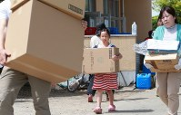 大人を手伝い、避難所に到着した支援物資を運ぶ女の子=熊本県益城町の広安小学校で2016年4月20日午後1時38分、兵藤公治撮影