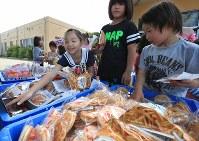 避難所に届けられたお菓子を好きなだけ手に取る子供たち。大量のお菓子は、震災のストレスで奇声を発したり、震えが止まらない子供たちを見て、地震発生初日から小学校に避難していた市村修一さん(32)が知り合いを通して長崎商工会から送ってもらった。市村さんは「辛いときには子供たちの笑顔が一番なので、硬い表情がとれただけでも良かったです」と子供たちを見つめていた=熊本県益城町の広安小学校で2016年4月20日午後1時14分、兵藤公治撮影