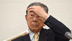 辞任を表明した記者会見で、額に手をやり記者の質問を聞くセブン&アイ・ホールディングスの鈴木敏文会長=2016年4月7日、徳野仁子撮影