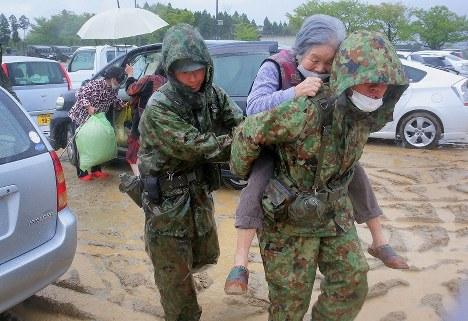 自衛隊員に背負われて小学校の体育館に向かう女性。16日の地震で倒壊した自宅から助け出され公民館に避難していたが、大雨でこの避難所へ移るよう指示された=熊本県阿蘇市で2016年4月21日午後2時11分、和田大典撮影