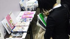 会場には企業のパンフレットがずらりと並び、ついつい手にしてしまう=マイナビ合同会社説明会で、竹内紀臣撮影