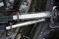 新名神高速道路工事現場で落下した橋桁(手前)=神戸市北区で2016年4月22日午後5時57分、本社ヘリから森園道子撮影