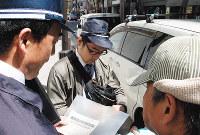 駐車禁止除外標章の不正使用を取り締まる警察官ら=大阪市中央区で2016年4月20日午前、宮嶋梓帆撮影