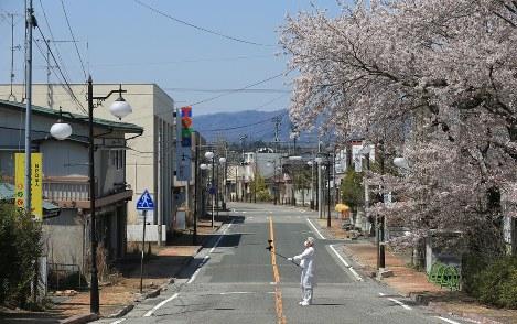 「原子力明るい未来のエネルギー」と記された看板があった町の目抜き通りでカメラを手に桜を撮影する大沼勇治さん=福島県双葉町で2016年4月、佐々木順一撮影