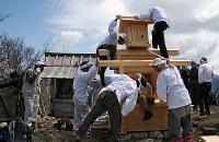新しく建てられた社に神様が移る「中之宮」を収める宮大工たち。左は古い社=滋賀県日野町の綿向山で、金子裕次郎撮影