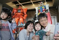 A family takes a photo in front of models of the Gundam and Zaku robots from the anime