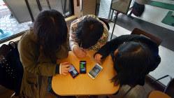 スマートフォンを使う高校生