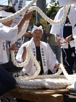 奉曳車を引く神聖な綱は、「お木曳き」参加者のなかを慎重に繰り伸ばされる。伸ばされた綱は腰より高い位置を保持しなければならない