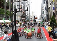 Participants try out the Paralympic sport of wheelchair basketball, in Ginza, Tokyo, on May 2, 2016. (Mainichi)