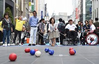 Participants try out the Paralympic sport of boccia, in Ginza, Tokyo, on May 2, 2016. (Mainichi)