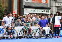 From left, wheelchair tennis players Satoshi Saida, Yui Kamiji and Shingo Kunieda, and Sydney Olympics women's marathon gold medalist Naoko Takahashi are seen at an event to experience Paralympic sports, in Ginza, Tokyo, on May 2, 2016. (Mainichi)