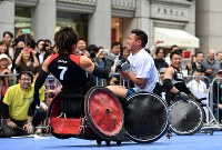 Rugby player for Japan's national team Akihito Yamada, right, grimaces as he is tackled by wheelchair rugby national team member Daisuke Ikezaki at an event to experience Paralympic sports, in Ginza, Tokyo, on May 2, 2016. (Mainichi)