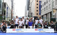 Wheelchair tennis player Shingo Kunieda, front center, members of the Japan national wheelchair rugby team, Tokyo Gov. Yoichi Masuzoe, third from right in the back row, and others pose for photographs, at an event to experience Paralympic sports, in Ginza, Tokyo, on May 2, 2016. (Mainichi)