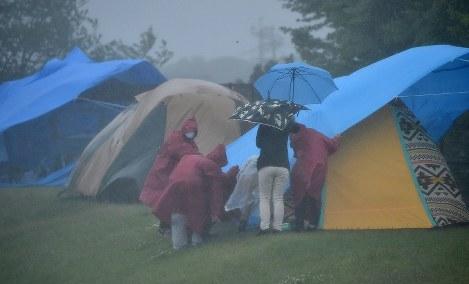 強い風雨で、被災者のテントの上にかぶせていたビニールシートが吹き飛ぶのを押さえるボランティアの人たち=熊本県益城町のグランメッセ熊本で2016年5月3日午後2時22分、川平愛撮影