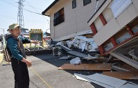 Kazumitsu Sosogi stands next to a collapsed apartment building in Mashiki, Kumamoto Prefecture, on April 29, 2016. Sosogi lived on the first floor with his wife and daughter. (Mainichi)