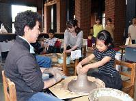 高井晴美さん(左)の指導でろくろを使い、陶器作りを体験する小学生=京都府舞鶴市の舞鶴赤れんがパークで、鈴木健太郎撮影