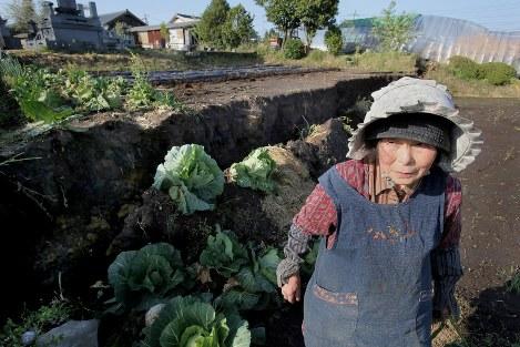 「本震」で沈下した畑を見つめる永富美津子さん(80)。4月17日が誕生日で家族で祝う予定だったが水や電気が止まり一時避難した。「いっぺんに十くらい年とった気持ち。こんな地震は昔話でも聞いたことがないけど、植えられるところに里芋を植えたよ。その季節にはその季節のものを植えないと気が済まないから」=熊本県阿蘇市で2016年4月22日、和田大典撮影