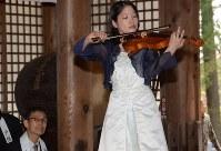 長野市産の木材と「奇跡の一本松」で作ったバイオリンの演奏を聴く中沢宗幸さん(左)=長野市の戸隠神社中社で
