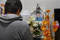 車中泊で亡くなった稲葉恵子さんの遺影の前に座る長男光彦さん=熊本県氷川町で(一部画像を処理しています)