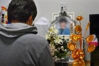 車中泊で亡くなった母恵子さんの遺影の前に座る長男の光彦さん=熊本県氷川町で2016年4月29日、今手麻衣撮影(一部画像を処理しています)