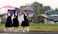 学校が再開され、地震で損壊した家屋の近くを歩いて通学する中学生=熊本県益城町で9日午前8時32分、幾島健太郎撮影