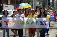 Tokyo Rainbow Pride representative co-directors, including Fumino Sugiyama, second from left, hold a banner as they walk at the front of the event parade on May 8, 2016. (Mainichi)