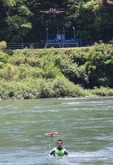 ドローンが運んだ浮輪を受け取る要救助者役の男性=美濃市前野の長良川で