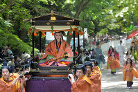 Saio-dai, a woman playing a royal maiden and shrine worshipper, center, and the rest of the Aoi Matsuri festival procession pass through the Tadasu no Mori forest at Shimogamo Shrine in Sakyo Ward, Kyoto, on May 15, 2016. (Mainichi)