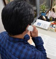 引きこもった自身の経験も踏まえ、電話相談に応じる男性=高松市内で、岩崎邦宏撮影